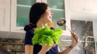 Slow motion of funny woman cook dance and sing with big ladle and lettuce while cooking in kitchen video