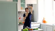 Slow motion of funny woman cook dance and sing with big ladle while cooking in kitchen at home video