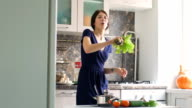 Slow motion of funny woman cook dance and sing with branch of lettuce while cooking in kitchen video