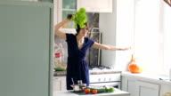 Slow motion of funny woman cook dance with green lettuce while cooking in kitchen at home video