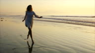 Slow motion of happy woman running on wet shore during sunset video
