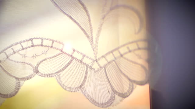 Slow motion of lace curtains floating in the breeze in close up hand held shot video