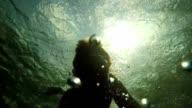 Slow motion of man jumping into waterhole, underwater shot video