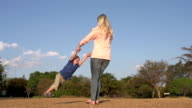 Slow motion of mother playing and swinging child around ,South Africa video