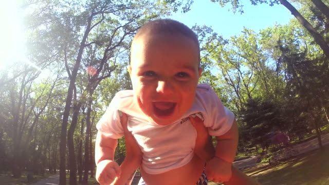 Slow motion of mother throwing his adorable a son in the air. video