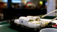 Slow motion of people eating California sushi roll video