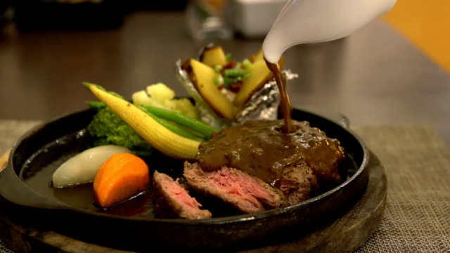 Slow motion of pouring black pepper sauce to beef steak video