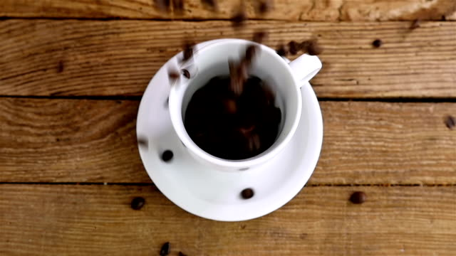 Slow motion of pouring coffee beans into a cup on an old wooden table, top view video