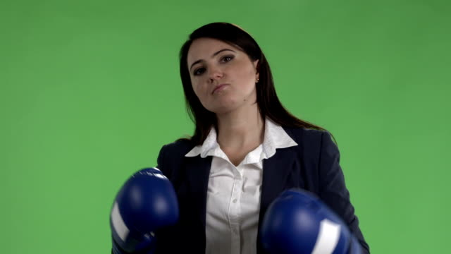 Slow motion of serious business woman with boxing gloves ready to fight against green screen video