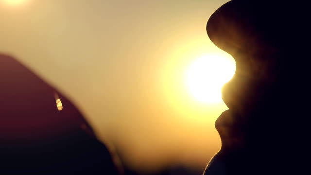 Slow motion of silhouette lips women blowing bubble at sunset city video