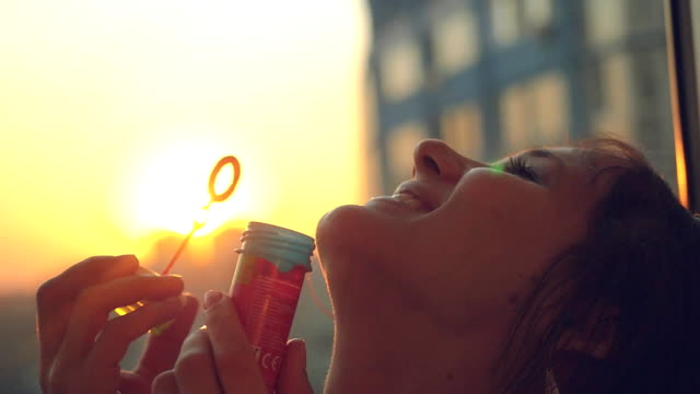 Slow motion of smiles young beautiful happy woman blowing bubble at sunset city video