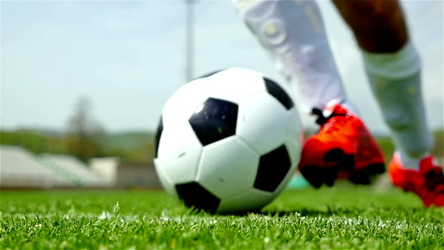 Slow motion of soccer player's feet dribbling a ball in front of the camera video