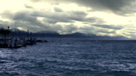 Slow motion of stormy waterscape, empty lakeside, heavy clouds above mountains video