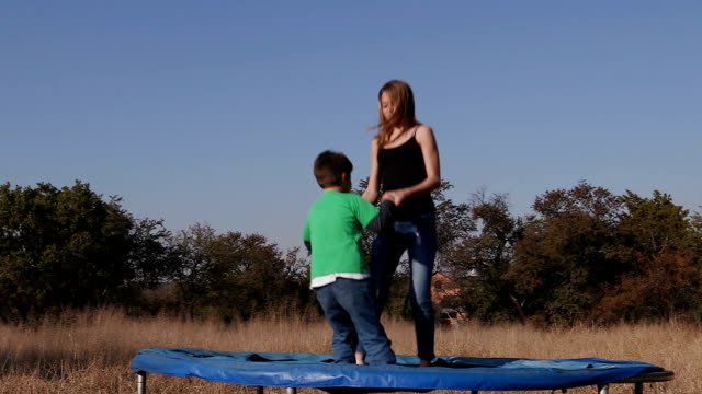 Slow motion of teenage girl and cute young boy having fun jumping on trampoline video