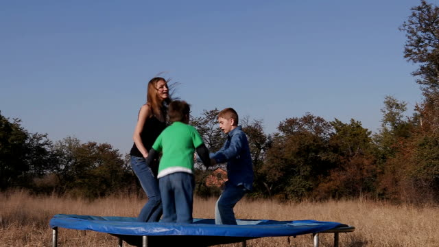 Slow motion of teenage girl and cute young boys having fun jumping on trampoline video