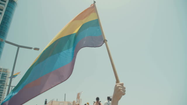 Slow motion of the pride flag waving during a pride parade video