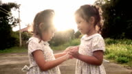 Slow motion of two Asian little girls standing hand in hand and encouraging each other video