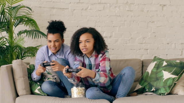 Slow motion of two mixed race curly girl friends sitting on couch play console computer games with gamepad and have fun at home video