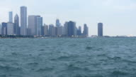 slow motion pan from Lake Michigan to Chicago skyline on cloudy grey day near dusk with waves. video