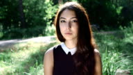 slow motion portrait of young attractive brunette looking at camera outdoor video