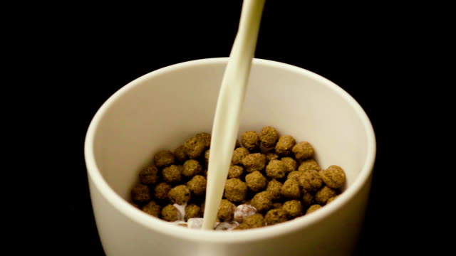 Slow motion pour the milk cereal chocolate balls video