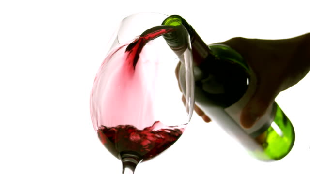 Slow motion pouring red wine on white background from below video