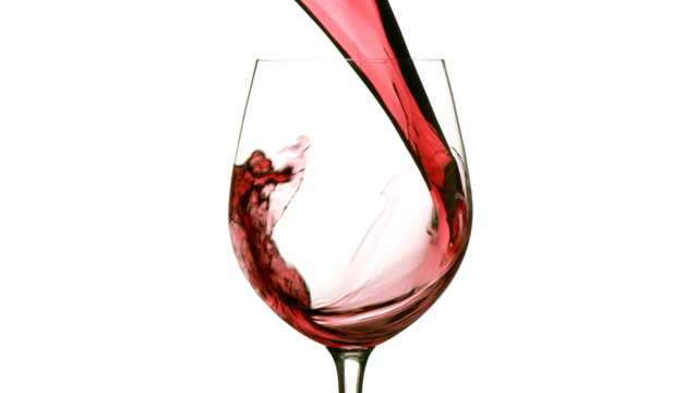 Slow motion pouring red wine on white background video