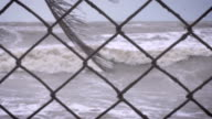 Slow motion rack focus on a chain link fence and a heavy surf from a storm video