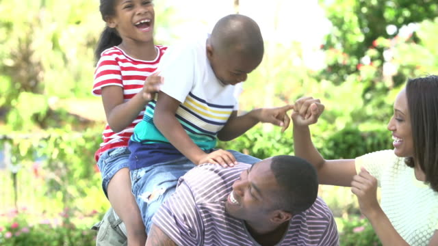 Slow Motion Sequence Of Children Riding On Father's Back video
