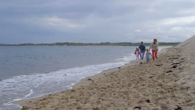 Slow motion sequence of family walking along sea shore with father carrying daughter on shoulders video