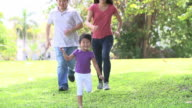 Slow Motion Sequence Of Parents And Daughter Running In Park video