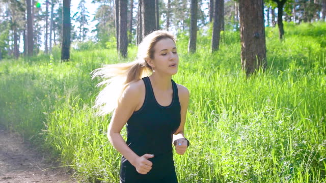 Slow motion shot of a young blonde woman in a sports suit, who actively runs through the park during the day, he enjoys the exercises video