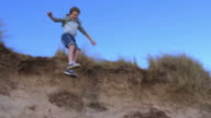 Slow Motion Shot Of Boy Jumping From Sand Dune video