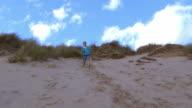Slow Motion Shot Of Boy Running Through Sand Dunes video