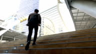 Slow motion shot of business man rushing up stairs to work in modern city video