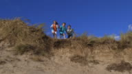 Slow Motion Shot Of Children Jumping From Sand Dune video