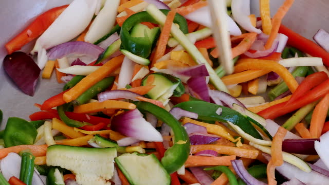 Slow motion shot of colourful thinly sliced vegetables being cooked in a pan video