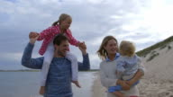 Slow Motion Shot Of Family On Beach Vacation Walking By Sea video