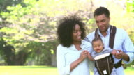 Slow Motion Shot Of Family With Baby Carrier Walking In Park video