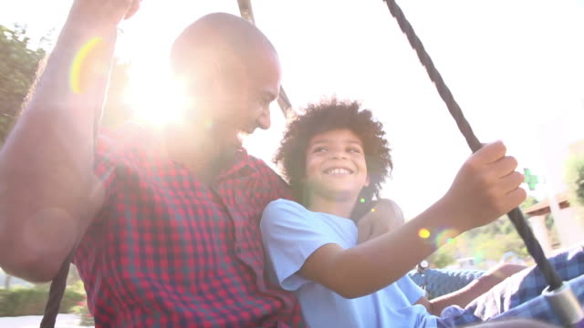 Slow Motion Shot Of Father And Son On Swing In Playground video
