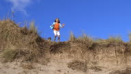 Slow Motion Shot Of Girl Jumping From Sand Dune video