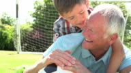 Slow Motion Shot Of Grandfather And Grandson With Football video