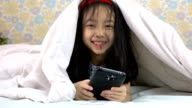 Slow motion shot of little girl using smartphone under the blanket video