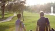 Slow Motion Shot Of Male Golfers Walking Along Fairway video