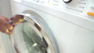 Slow Motion Shot Of Man Putting Laundry Into Washing Machine video