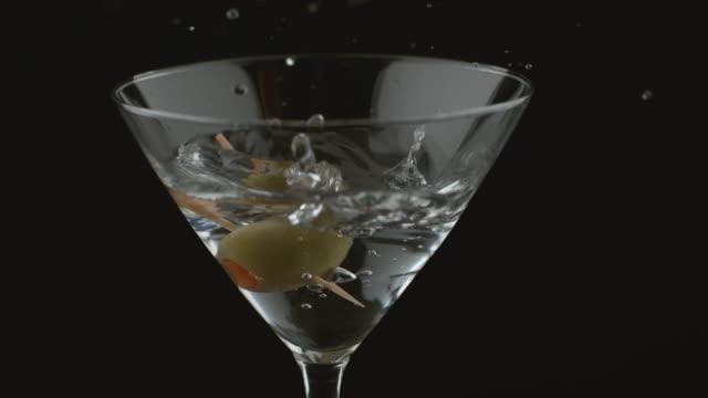 Slow motion shot of olive splashing into martini video