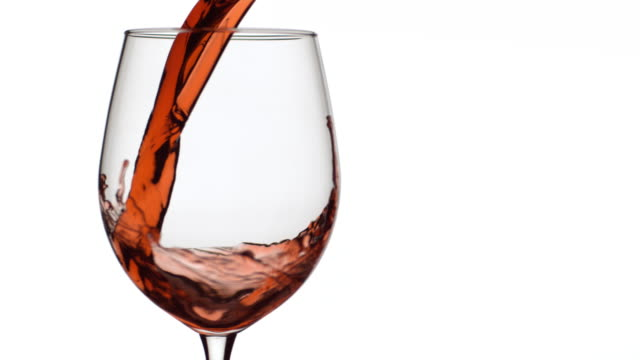 Slow motion shot of red wine pouring into glass on white background video