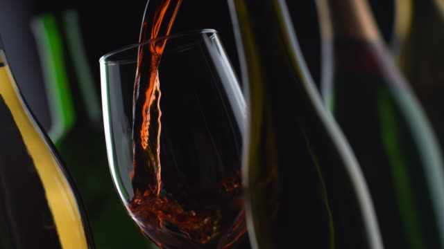 Slow motion shot of red wine pouring with bottles and black background video