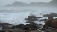 Slow motion shot of stormy waves crashing over a rocky beach in Scarborough, South Africa video