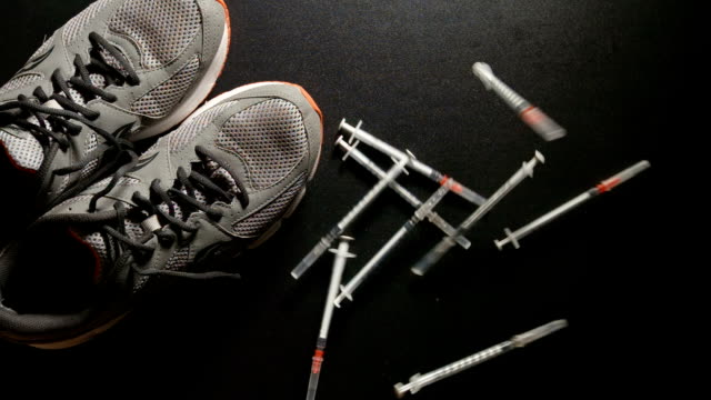 DOPING: Slow motion shot of Syringes fall near a sneakers - top view video
